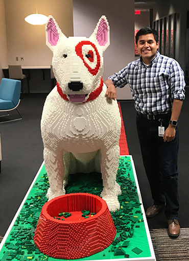 Hector stands to the right of a statue of Bullseye the dog made of LEGOs.