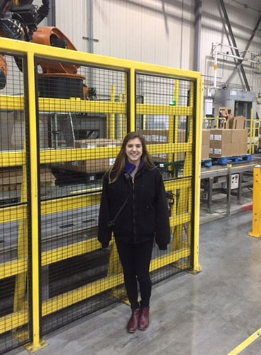 Kellie stands in the DC in front of a yellow shelf and cardboard boxes on a conveyor belt