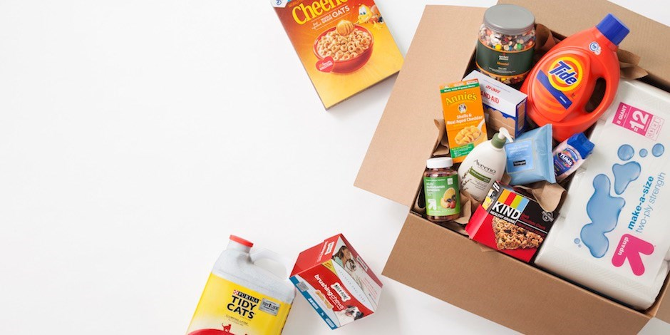 A cardboard box with essentials products spilling out onto a white background