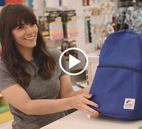 Naomi Davis in a Target store holding up a navy blue Yoobi backpack