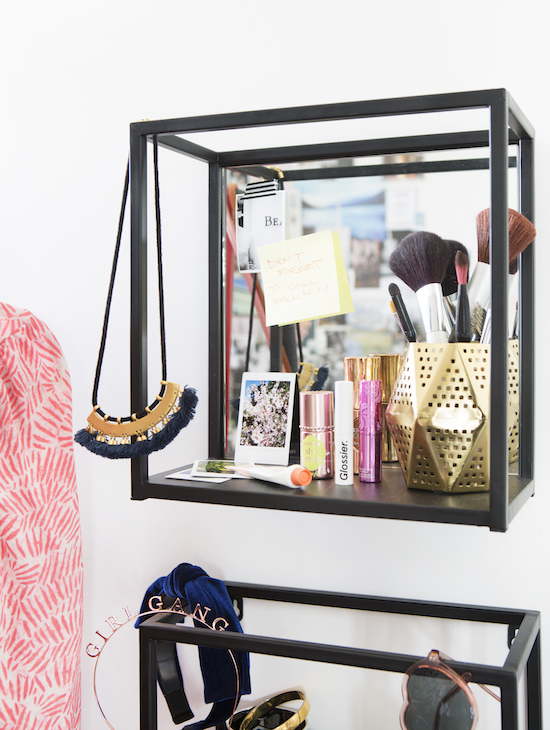 A mirrored shelf with makeup and jewlery