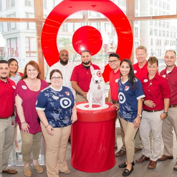 Target team members in red and khaki pose with Bullseye in front of a red Bullseye logo.
