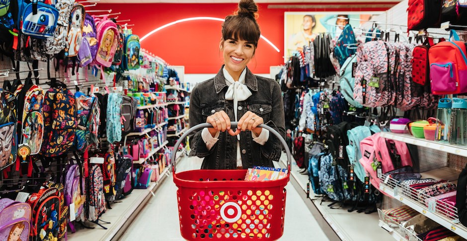 Naomi Davis standing in a Target aisle, holding a basket and surrounded by backpacks