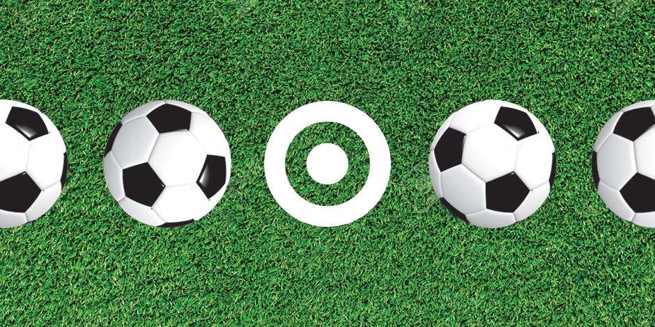 A white Target bullseye logo on green grass between four soccer balls