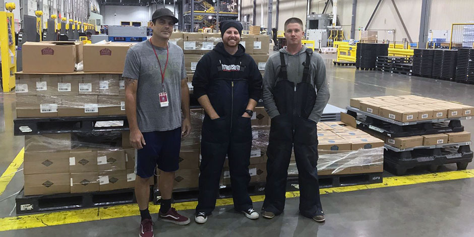 Team members Eric, CJ and Andy stand in front of a pallet at their FDC.