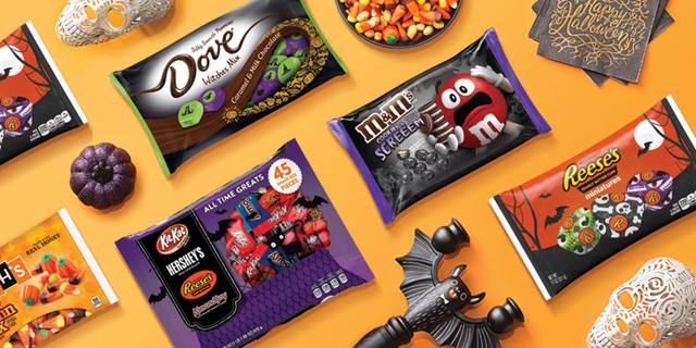 Bags of Halloween candy and Halloween figures against an orange background