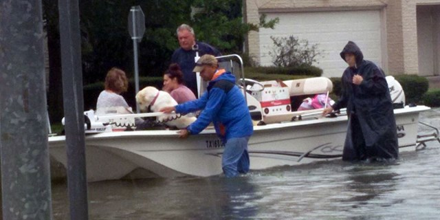 A team member pushes a boat through a flooded street with people and pets inside