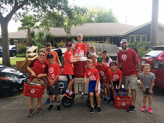 Volunteers and kids with coolers and Target baskets standing in front of a house and cars