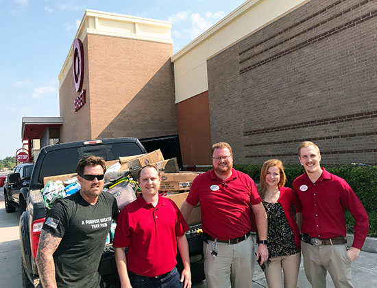 Four team members and war veteran Marcus Luttrell stand in front of a Target store with a pickup truck full of donations