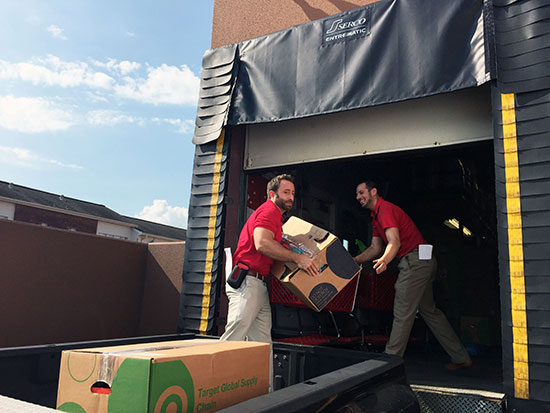 Two team members unload boxes of supplies from a trailer