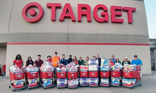 Team members lined up in front of their store with carts full of product donations