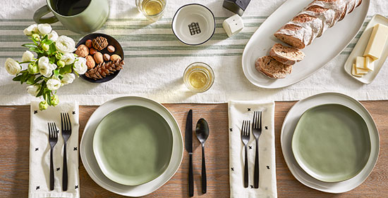 A table set with cream and sage green settings and copper tableware