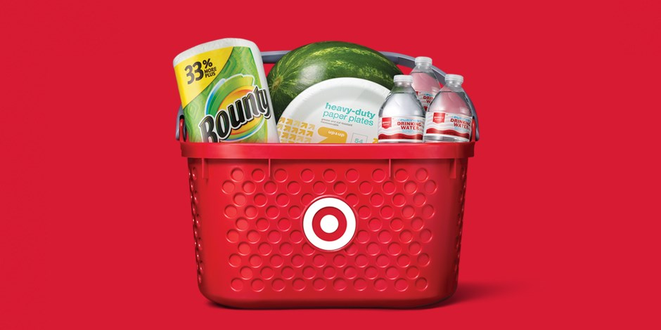 A red Target basket full of paper towels, paper plates, water and a watermelon