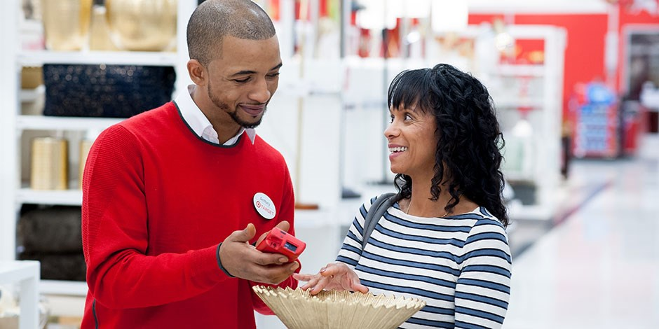 A team member in a red shirt helps a guest shopping in the Home aisles