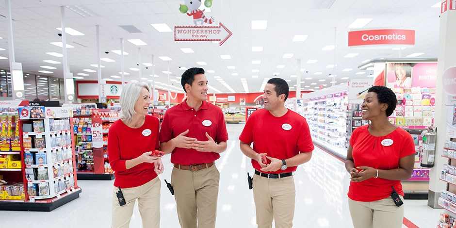 Four team members in red and khaki walk a Target aisle, talking and laughing