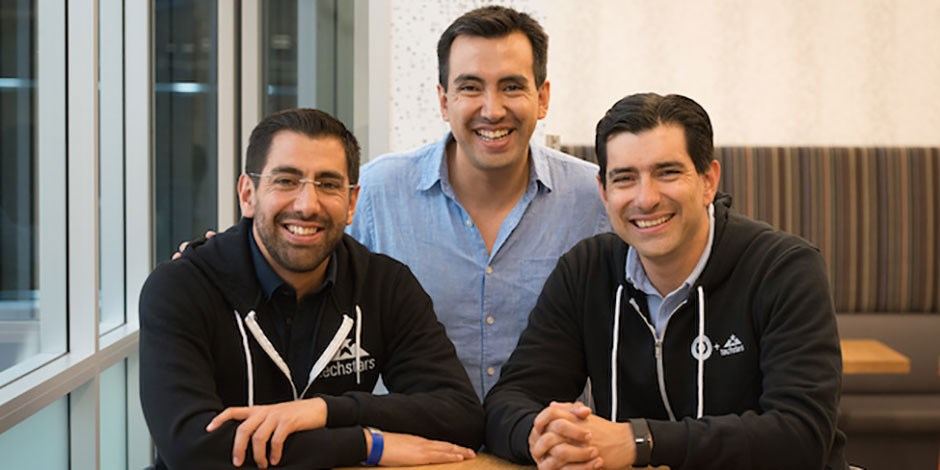 Inspectorio founders Carlos, Fernando and Luis sit at a table, smiling.