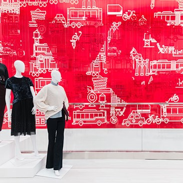 Three mannequins against a red mural