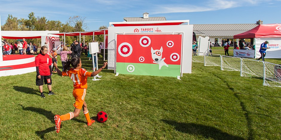 A girl kicks a soccer ball at a goal with Bullseye the dog and Target logos