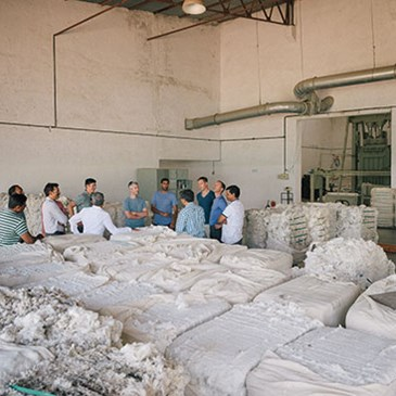 A circle of team members and cotton producers stand talking in a facility