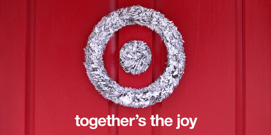 "A sliver tinsel bullseye wreath hangs on a red wall, alongside ""together's the joy"""