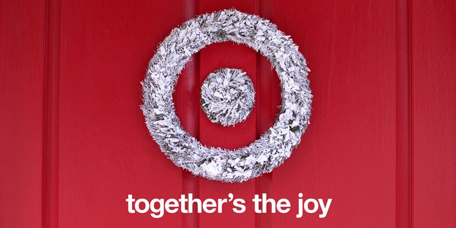 A sliver tinsel bullseye wreath hangs on a red wall, alongside