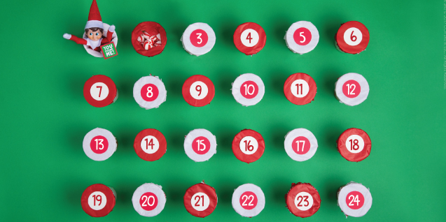A red and white countdown calendar, with an elf popping out of one of the cups