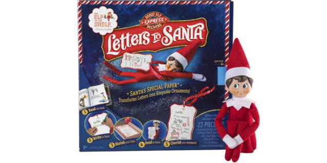 "An elf sits next to ""Letters to Santa"" packaging"