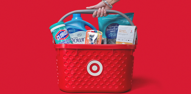 A hand grabs a Target basket, filled with chips, fabric softener, coffee and more