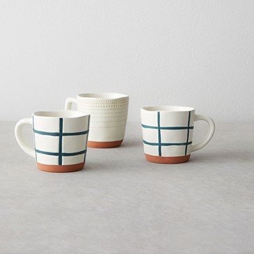 Cream colored mugs with blue accents and terracotta bottom and side handles