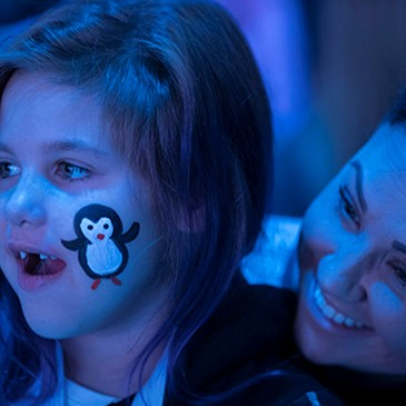 A girl with a penguin painted on her cheek watches the ballet with her mom