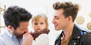 Nate Berkus holding daughter Poppy with husband Jeremiah