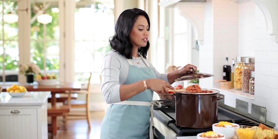 Ayesha Curry cooking in a brown pot on her stove