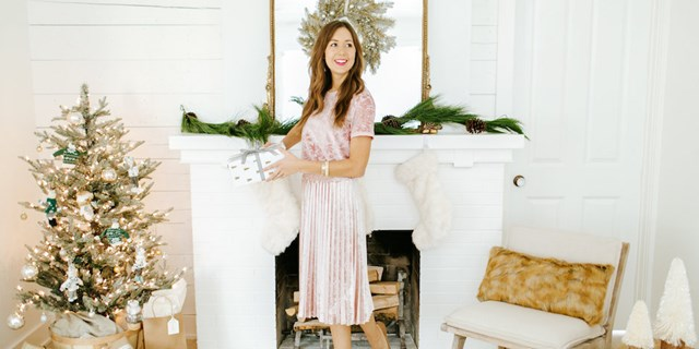 Camille Styles holding a wrapped gift standing in front of a decorated mantle