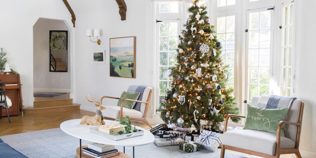 Emily Henderson's living room decorated for the holidays with a tree, presents and seasonal decor