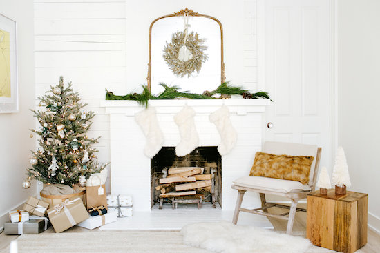 Decorated living room with stockings hung above a fireplace mantle, a decorated tree and more