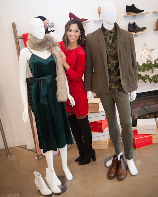 Karla styling two mannequins in festive holiday outfits