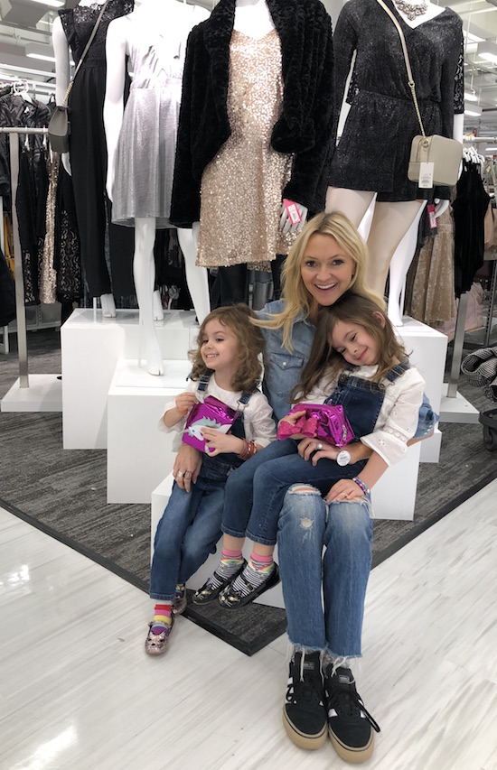 Zanna and her daughters sitting by a women's holiday clothing display