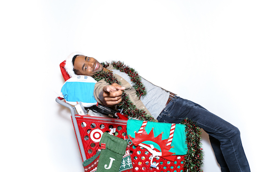 Jay Ellis on a Target shopping cart filled with gifts
