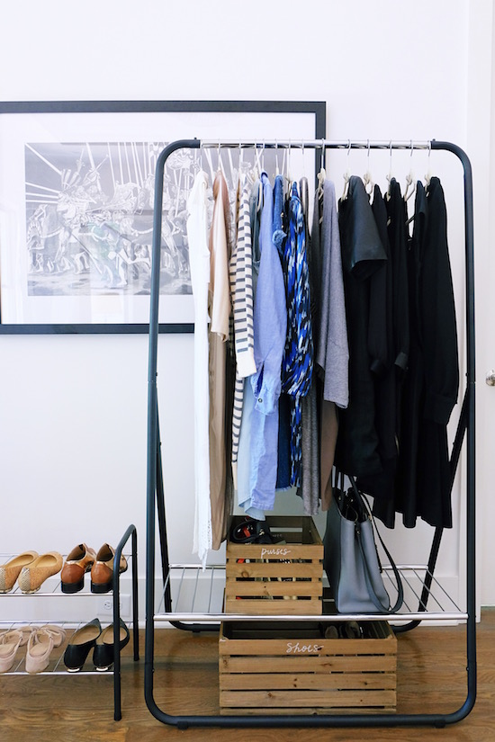 Organized clothing on a closet rolling rack with shoe and purse bins below
