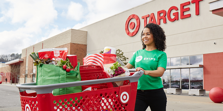 A woman in a green Shipt t-shirt pushes a cart filled with products in front of a Target store