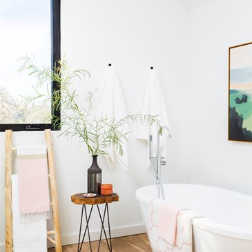 white tub with new towels and stool with plant