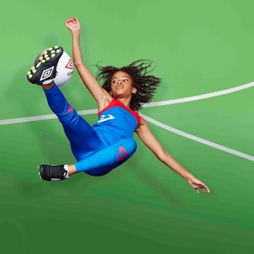 A girl kicks a ball