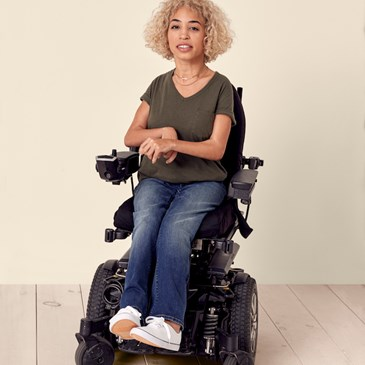 Model in wheelchair wearing denim and olive t-shirt