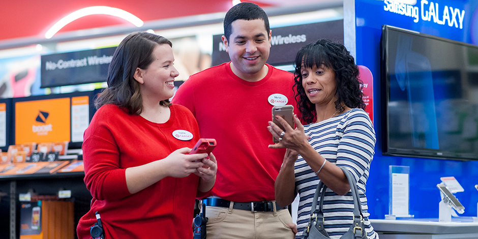 Two team members help a guest with her smartphone in the Electronics department