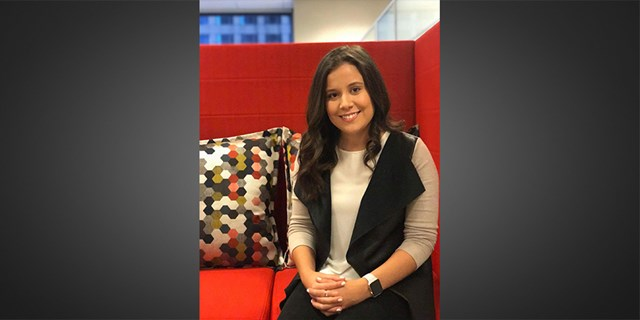 Laura H. sitting on a red couch at Target headquarters