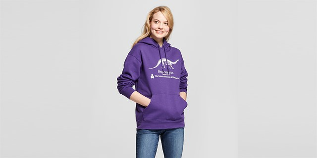girl wearing purple sweatshirt with dinosaur print