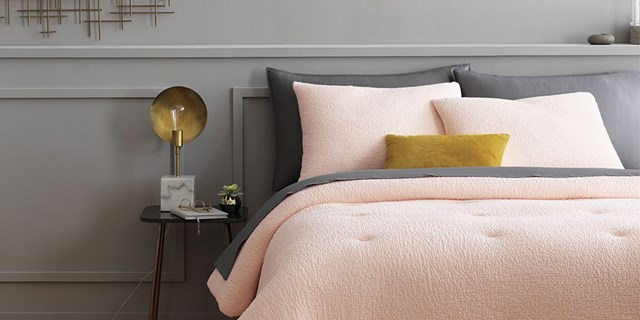 A bed with dark grey and pale pink bedding, finished with a yellow throw pillow