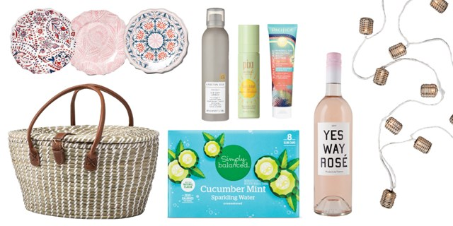 A variety of summer goodies, including picnic basket, plates, beauty product, sparkling water, rose