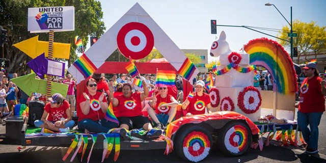 Team members ride on and walk alongside Target's float in the Phoenix Pride Parade