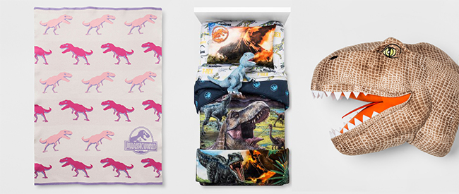 A blanket featuring pink T.rex, a bed decked out in dino gear and a T.rex head pillow